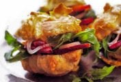 Gougeres, or cheese puffs, with arugula, bacon, and pickled onion on a metal plate