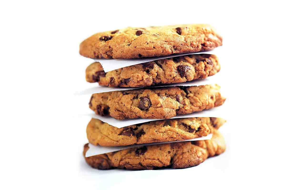 A stack of Neiman Marcus chocolate chip cookies separated by pieces of parchment.
