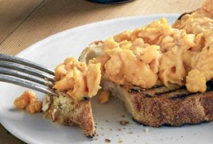 Slice of toast with scrambled eggs drizzled with truffle oil on a plate