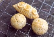 Three cookies--two balls, one oblong--with circular and perforations decorations on top on a wire rack