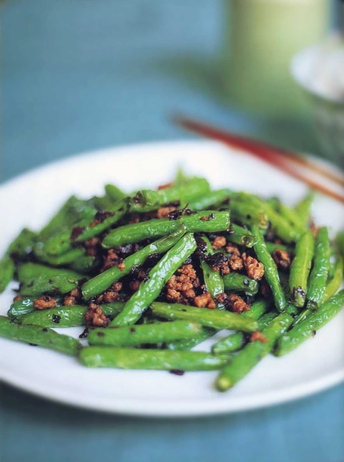 Plate of dry-fried green beans with cooked ground pork, chopsticks, on a blue background