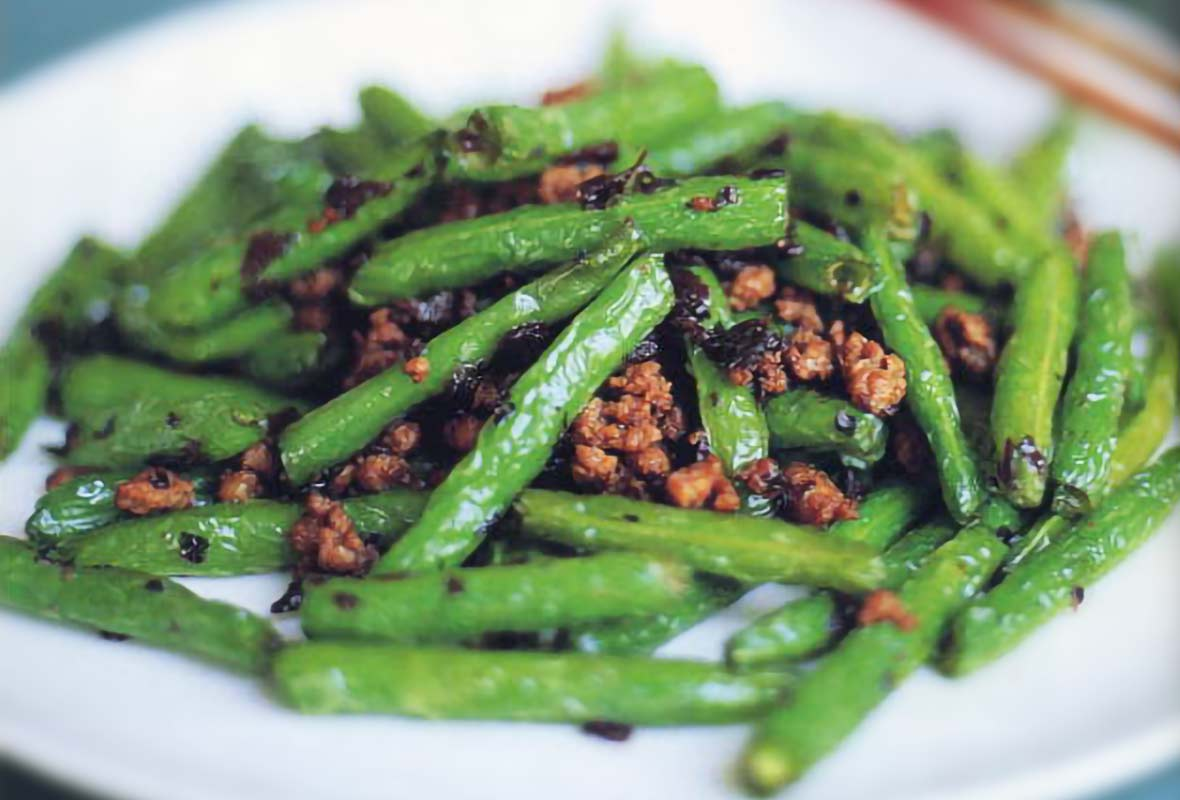A white plate with dry-fried green beans with bits of cooked ground pork