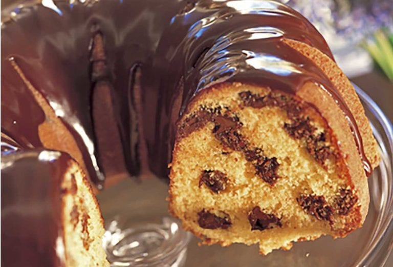 Orange Bundt cake, with a sliced removed, studded with chocolate chips and topped with chocolate ganache