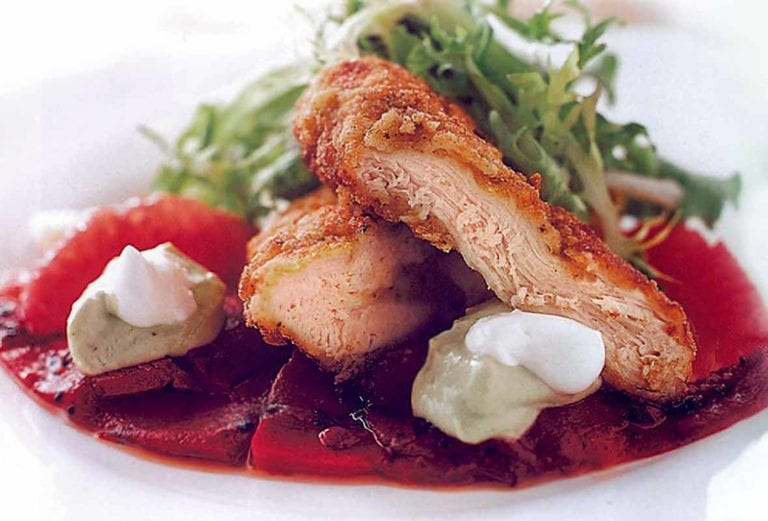 Sliced masa-crusted chicken breast with piquillo peppers, avocado butter, and salad on a plate