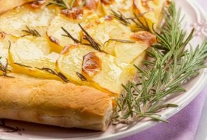 A potato rosemary focaccia--bread topped with sliced potatoes and rosemary sprigs on a white plate