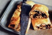 Two mushroom strudels on a silver tray, one cut in half, with a knife resting on top.