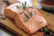 Filet of salmon topped with rosemary leaves on a cedar plank
