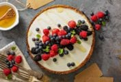 A red, white, and blue tart with a graham cracker crust, cream cheese filling, and raspberries, blueberries, and blackberry on top