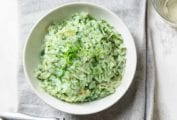 A white bowl filled with spinach and arugula risotto on a grey linen napkin.