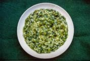 White bowl of spinach and arugula risotto on a green background