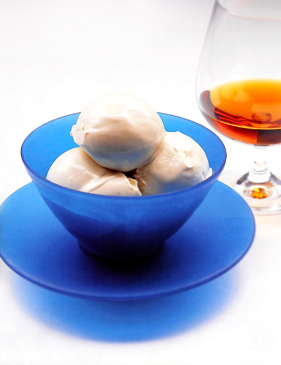 A blue glass bowl fill with creamy, white Armagnac ice cream, a snifter of Armagnac behind