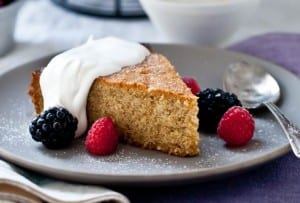 A slice of honey walnut cake, topped with whipped cream and fresh berries.