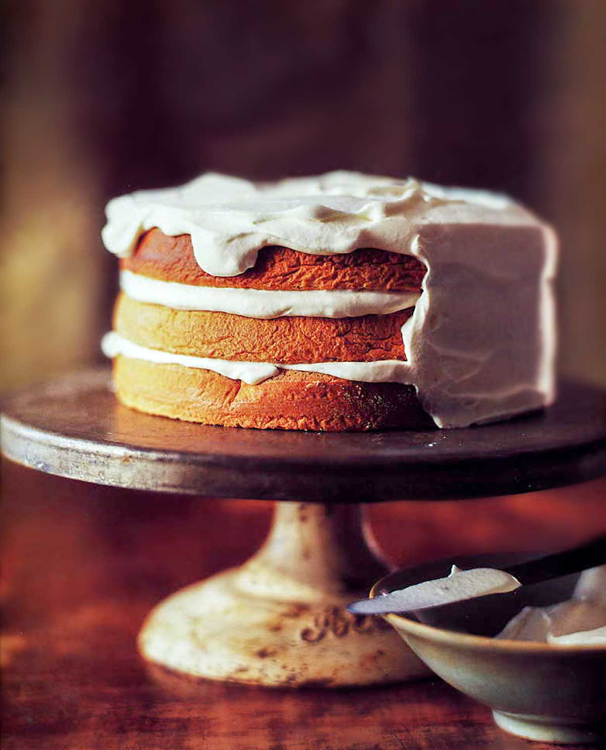 A partially frosted three-layer walnut torte on a vintage cake stand with a bowl of whipped cream and a knife beside it.