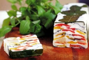 A loaf of tomato-goat cheese terrine--garlicky goat cheese layered with red and yellow tomatoes and arugula on a cutting board