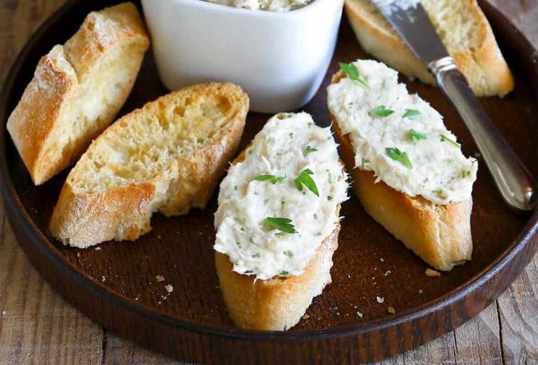 A plate with five baguette slices, a knife, and white bowl filled with fresh cod brandade, garnished with parsley.