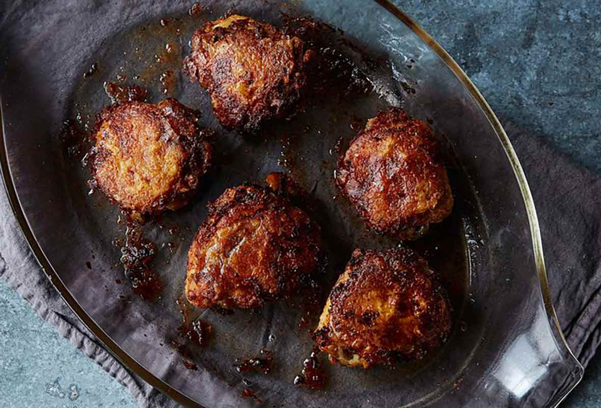 A casserole dish with five chicken thighs that have been oven-fried set on top a dish towel