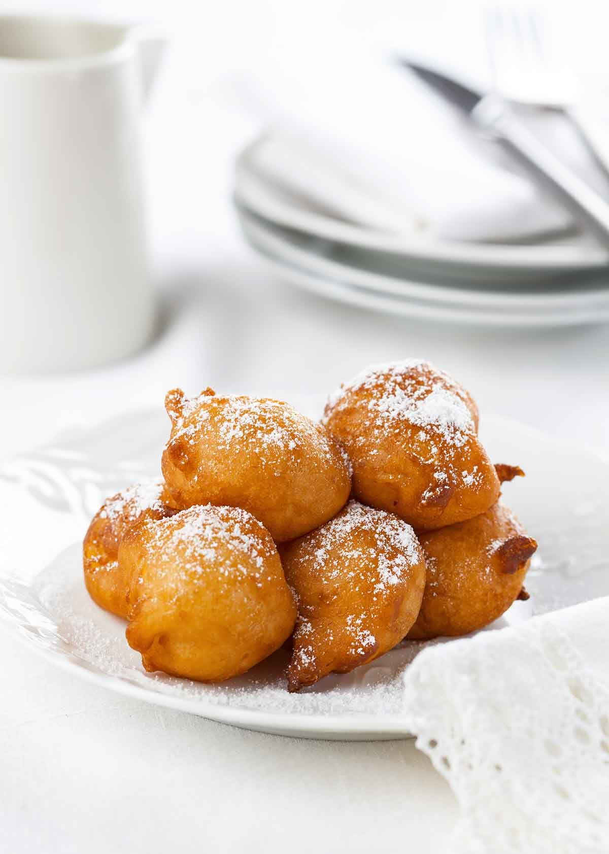 A pile of ricotta-sweet potato beignets dusted with confectioners' sugar on a white plate.