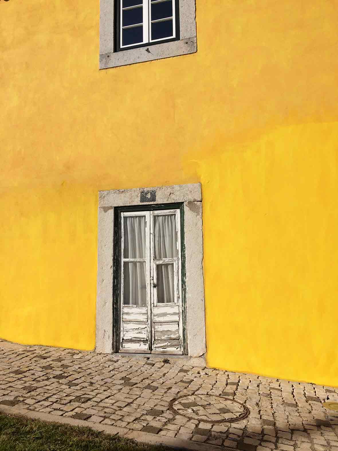 Door in a yellow wall in Lisbon