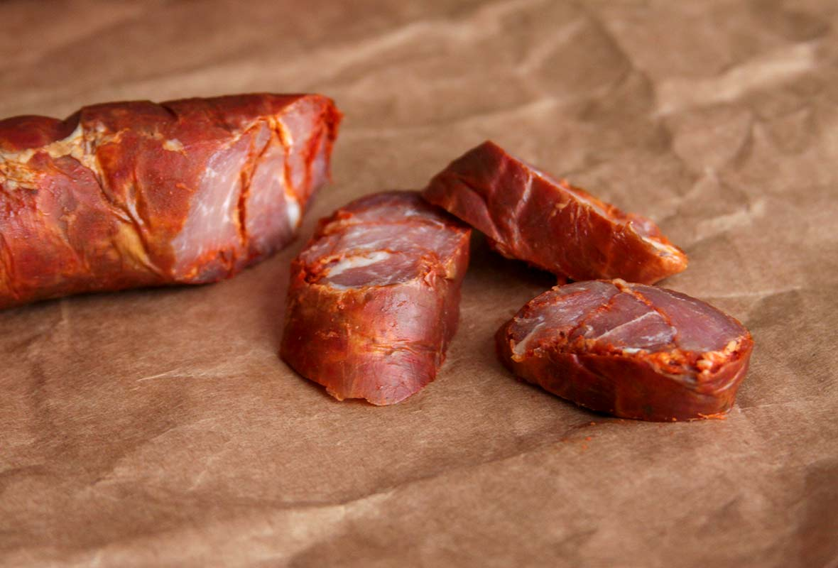 A link of Portuguese chouriço sausage with three slices on butcher paper