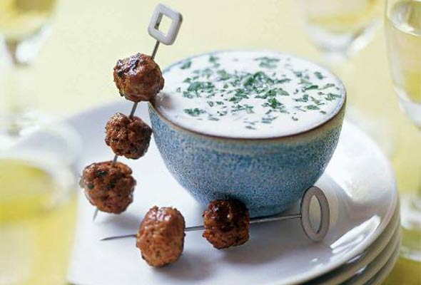 Two lamb meatball skewers resting beside a dish of yogurt sauce.