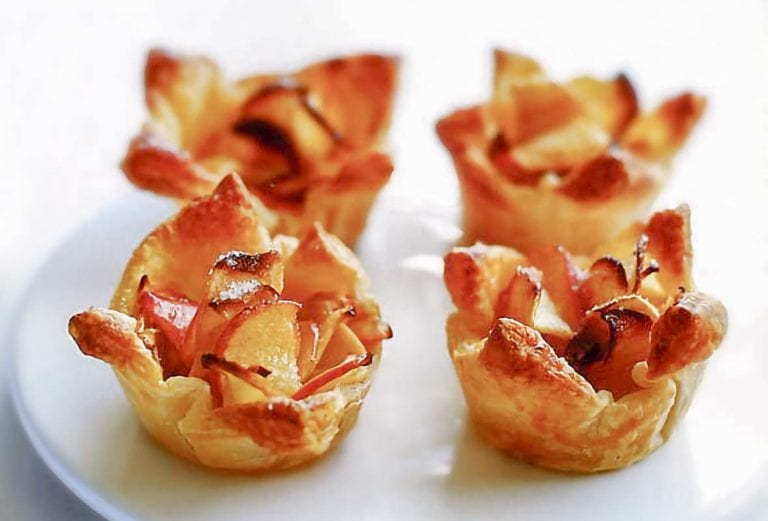 Four mini apple tarts made from apple slices in puff pastry shells on a plate