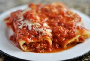 White plate with two rolled manicotti on it