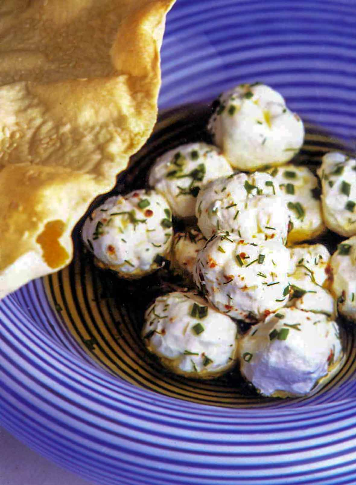 Yogurt cheese balls tossed with garlic dill oil and aleppo pepper in a bowl