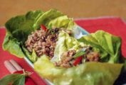 Butter lettuce leaves cradling ground dark chicken in bowl