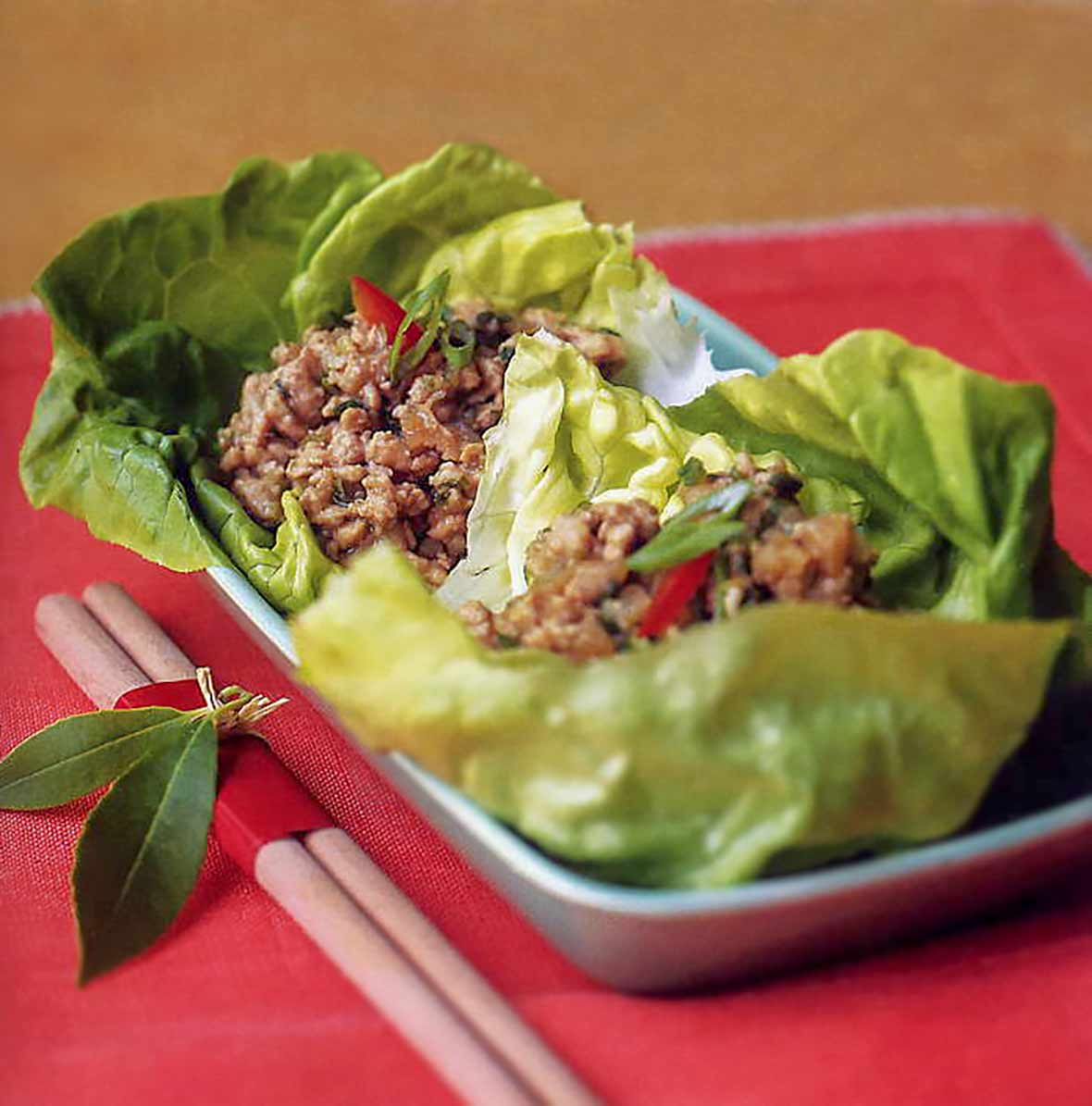 Butter lettuce leaves cradling ground dark chicken in bowl, chop sticks on the side
