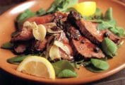 Plate of grilled beef, rosemary, capers, salad greens and lemon wedges
