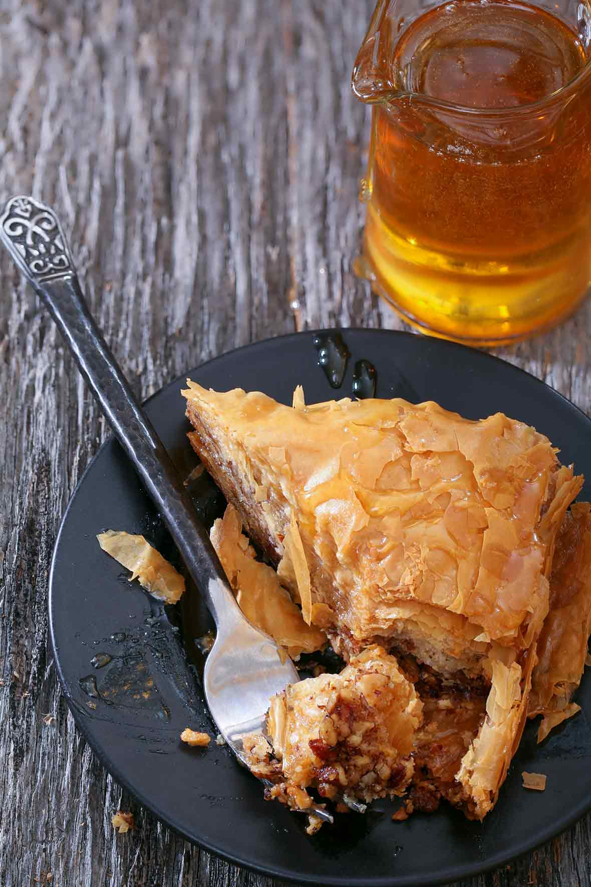 Triangular piece of Greek baklava, with layers of filo or phyllo dough filled with chopped walnuts, drizzled with honey on a black plate