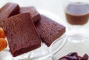 Slices of a chocolate mousse cake on a glass cake stand with fruit compote on the side