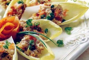 Endive leaves stuffed with cream cheese spread with smoked salmon with chopped chives on top