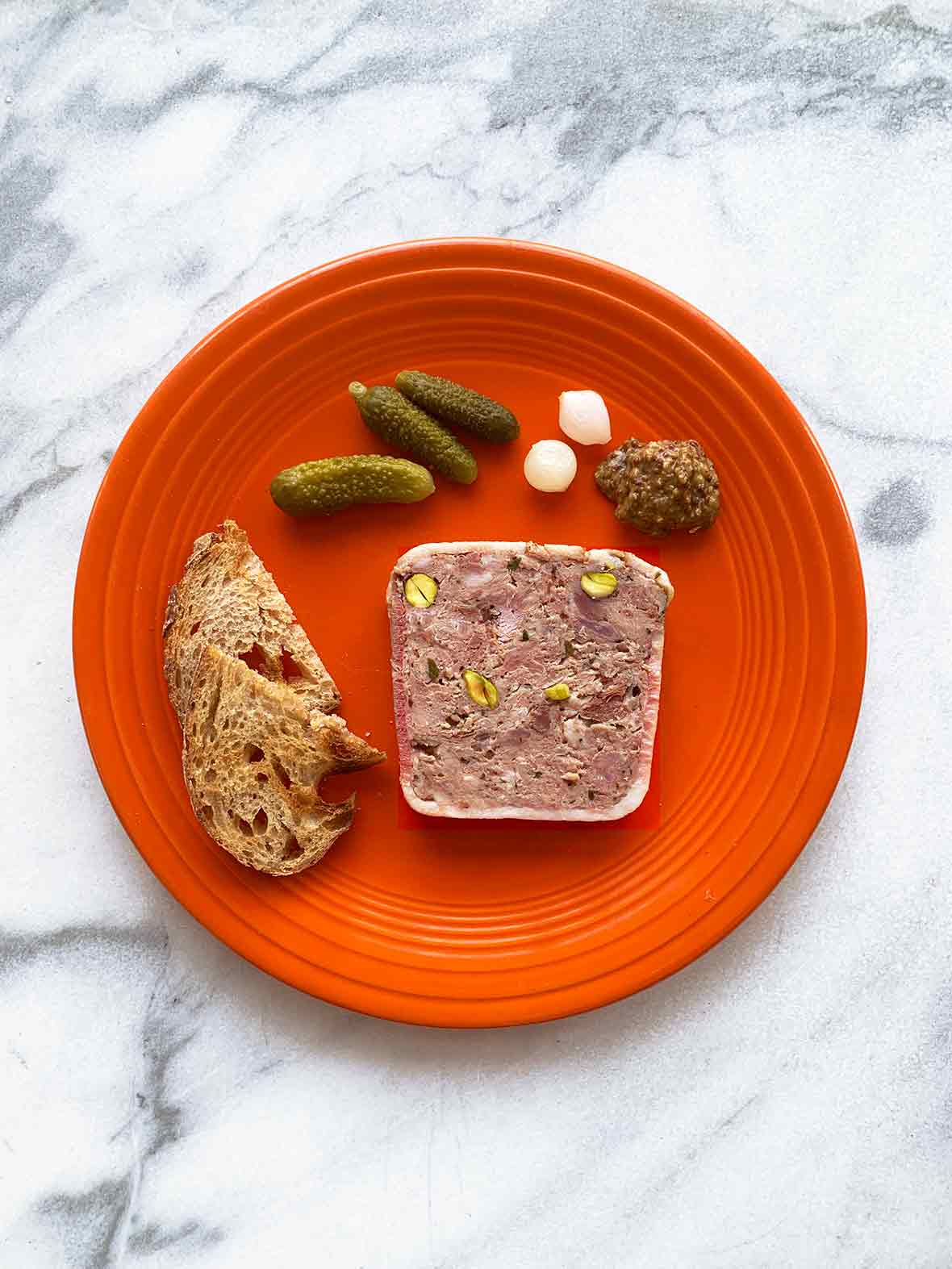 A red plate with a slice of pate de campagne, crostini, cornichons, pickled onions, and a dollop of mustard