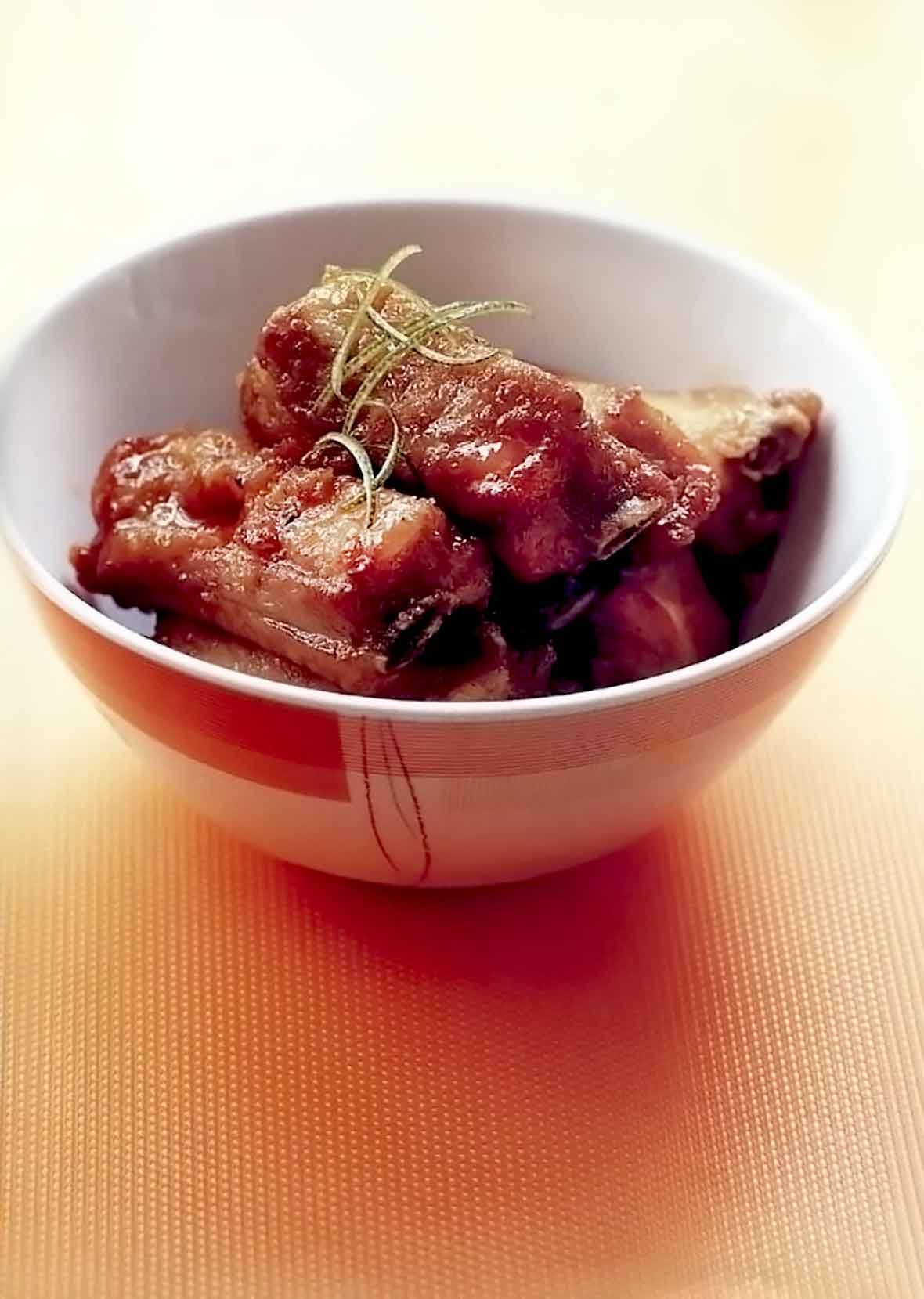 A bowl with three spare ribs glossed with a sweet-sour sauce, on top lime zest