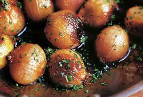 A skillet filled with Ina Garten's caramelized shallots, sprinkled with parsley.