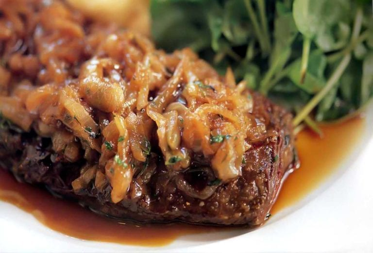 Skirt steak topped with caramelized shallots on a plate with pan juices and arugula salad