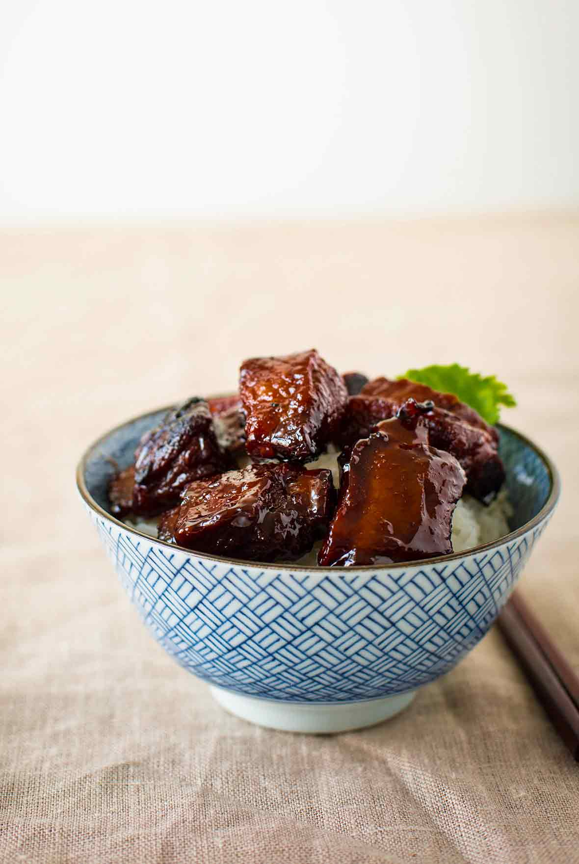 A blue and white Chinese bowl with sweet and sour spareribs in side, garnished with parsley