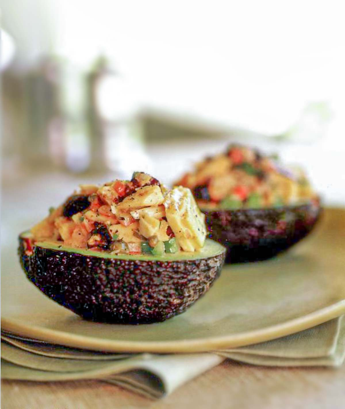 Two avocado halves filled with fresh tuna with dry-cured black olives.