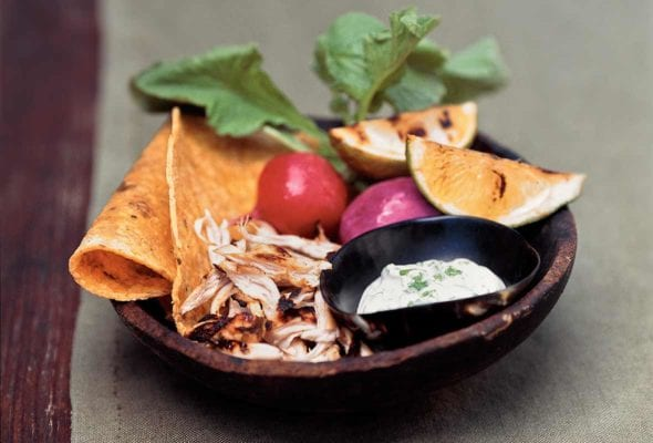 Wood bowl with tequila-lime chicken tacos, charred limes, radishes, sour cream