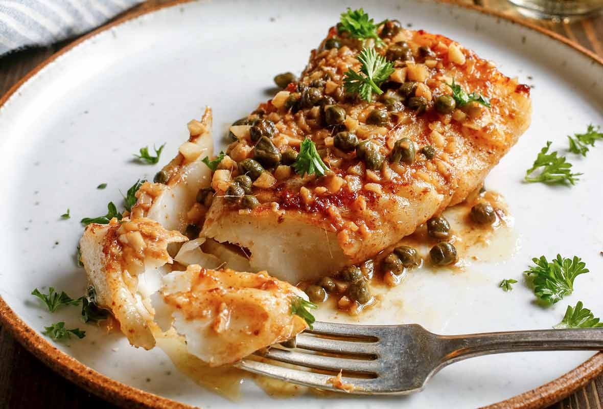 Pan-roasted halibut with caper vinaigrette on a white plate sprinkled with parsley
