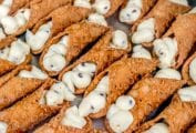 Sheet pan of 2 dozen cannoli filled with sweet ricotta filling and chocolate chips