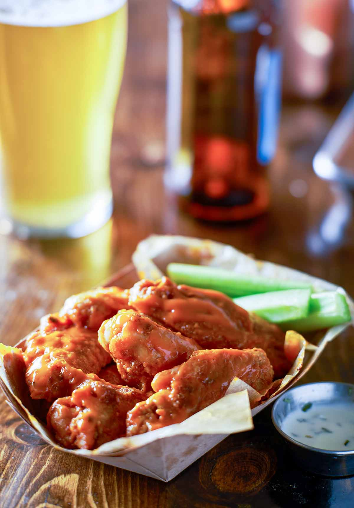 A paper basket filled with classic buffalo wings and celery sticks with a metal cup of dipping sauce beside it.