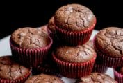 A white plate with a stack of chocolate muffins in red liners.