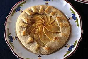 Individual rustic apple tart with the crust folded over a filling of sliced apples on a flowered plate