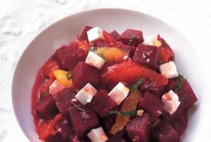A white bowl filled with a beet salad with feta and orange and sliced mint leaves