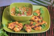 Green plate with six grilled coconut wings, with grill marks, topped with cilantro, nearby a dish of Thai peanut sauce