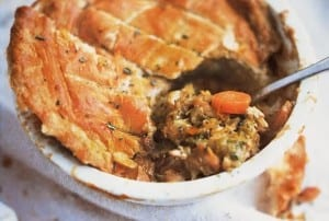 A white individual pie dish filled with chicken and leek pot pie, topped with puff pastry and a spoon resting inside.