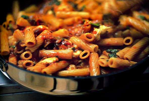 A skillet filled with rigatoni with tomatoes, eggplant, and mozzarella.