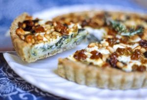 A swiss chard, leek, and goat cheese tart on a white platter with one slice being cut.